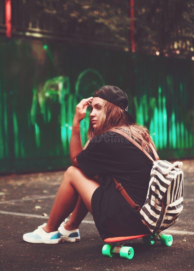 Girl sitting on plastic orange penny shortboard royalty free stock images