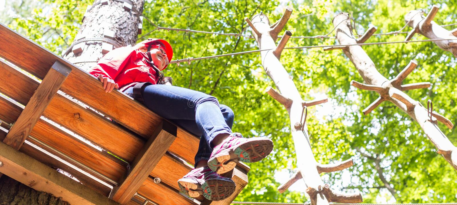 Girl sitting on platform in high rope course resting. Girl resting on platform in high rope course royalty free stock photography