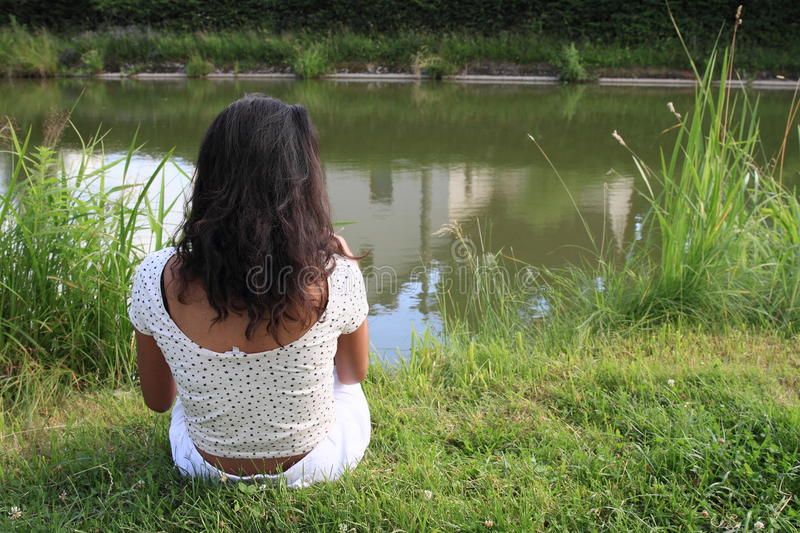 Girl sitting by pond stock photography