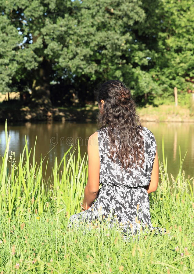 Girl sitting by pond stock image