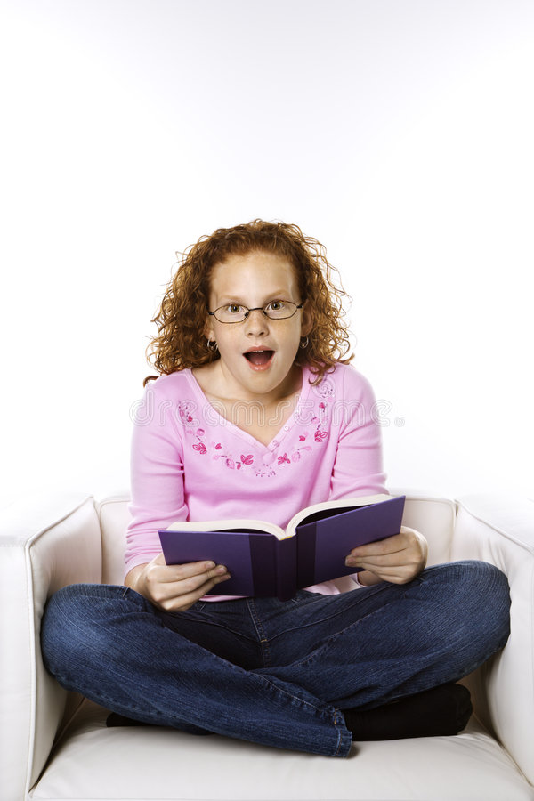 Girl sitting reading book looking surprised. stock image