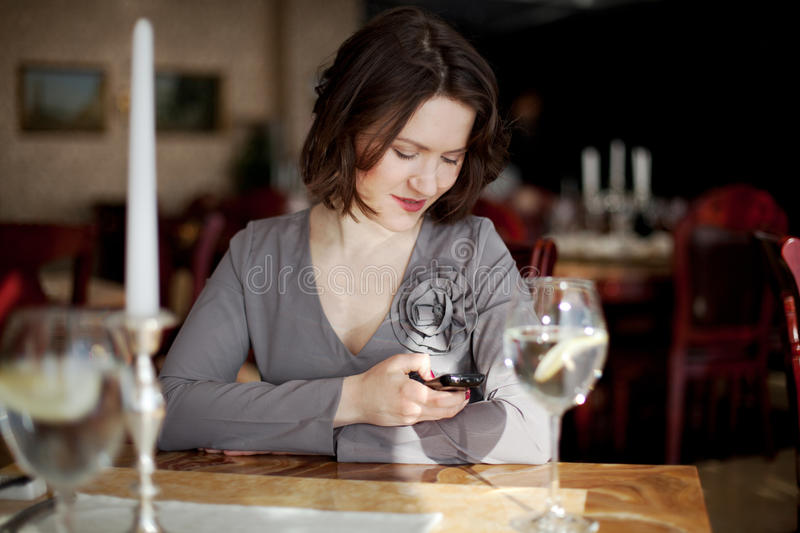 A girl sitting in a restaurant. Girl is sitting in a restaurant, she reads the message on the phone royalty free stock image
