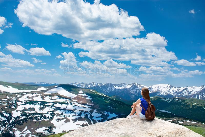 Girl sitting on the rock on hiking trip in beautiful mountains. royalty free stock photo