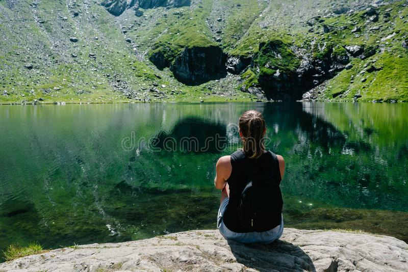 A girl sitting on a rock, looking at a spectacular view of the mountain reflecting in the lake. royalty free stock photo