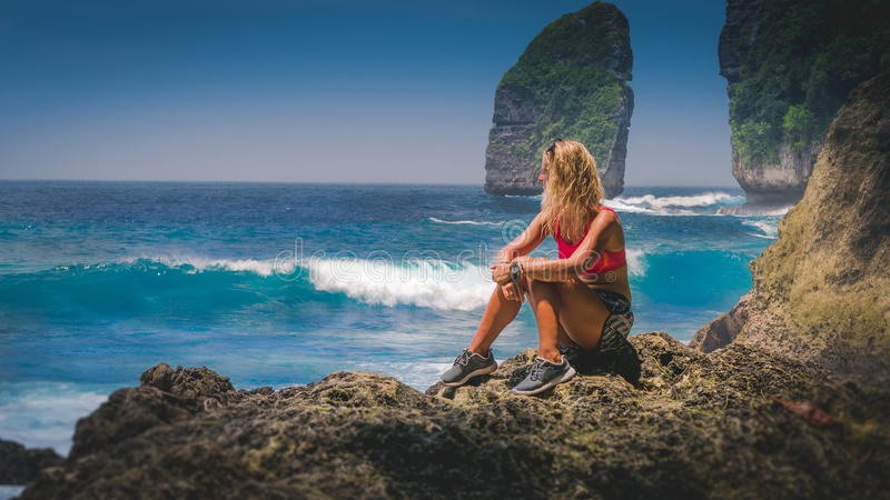 Girl sitting on the Rock and watching Huge Waves hitting Tembeling Coastline at Nusa Penida Island, Bali Indonesia.  stock images