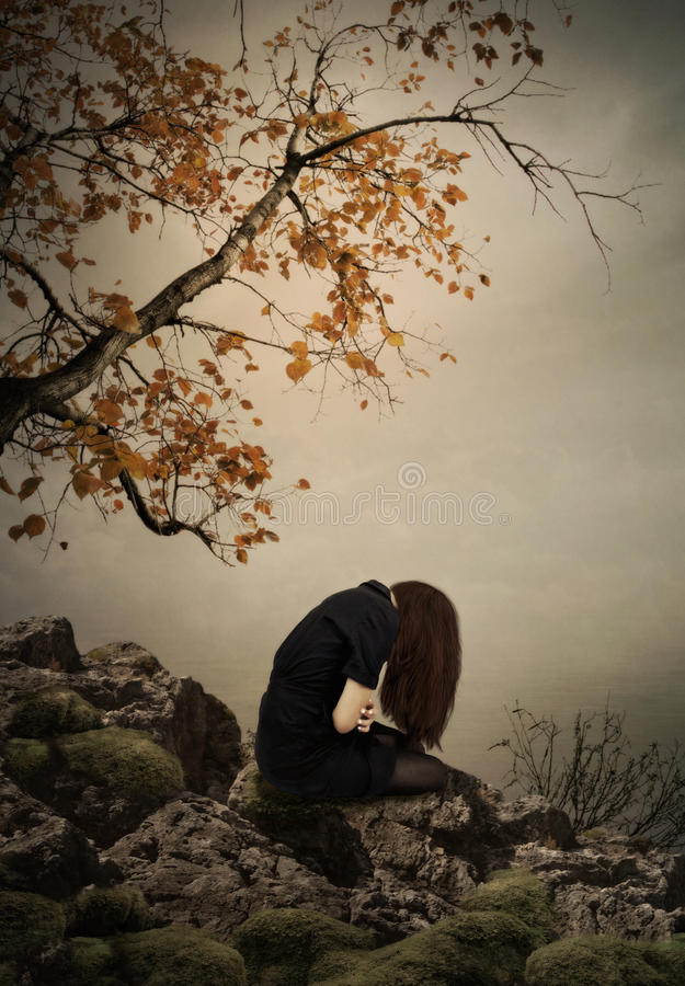 The girl sitting on a rock royalty free stock image