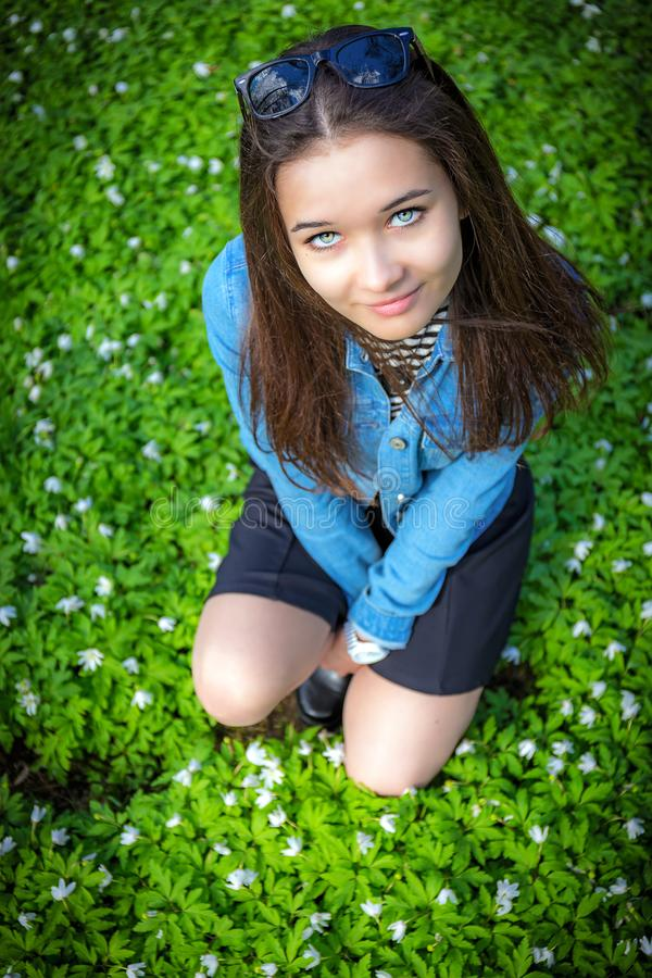 The girl is sitting among the snowdrops. stock photos