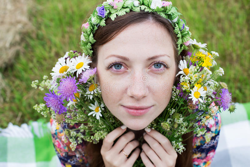 Girl sitting with splitting flower bouquet. Freckled girl sitting with splitting wild flower bouquet royalty free stock photo