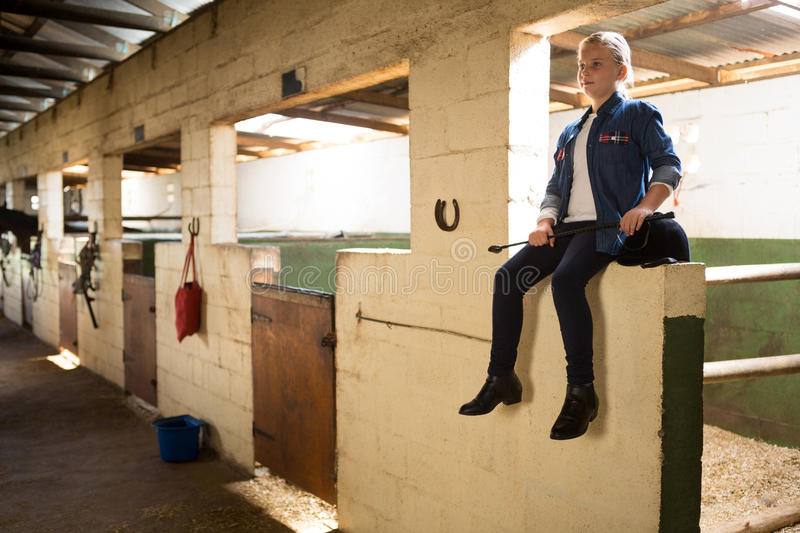 Girl sitting in stable stock images