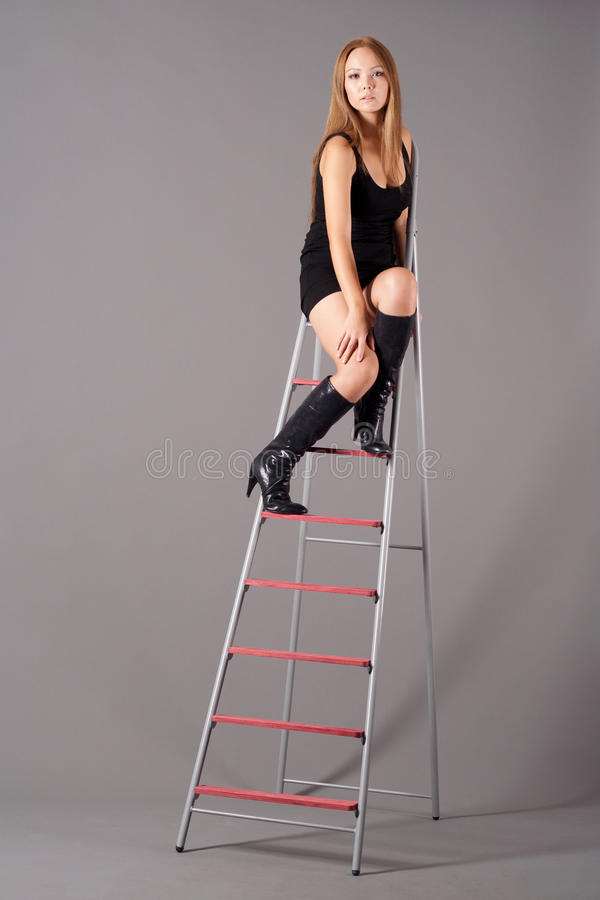 Girl sitting on a stepladder royalty free stock image
