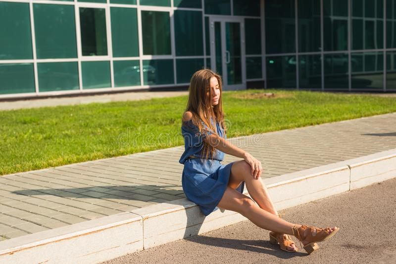 Girl sitting on street in summer day.  stock photos