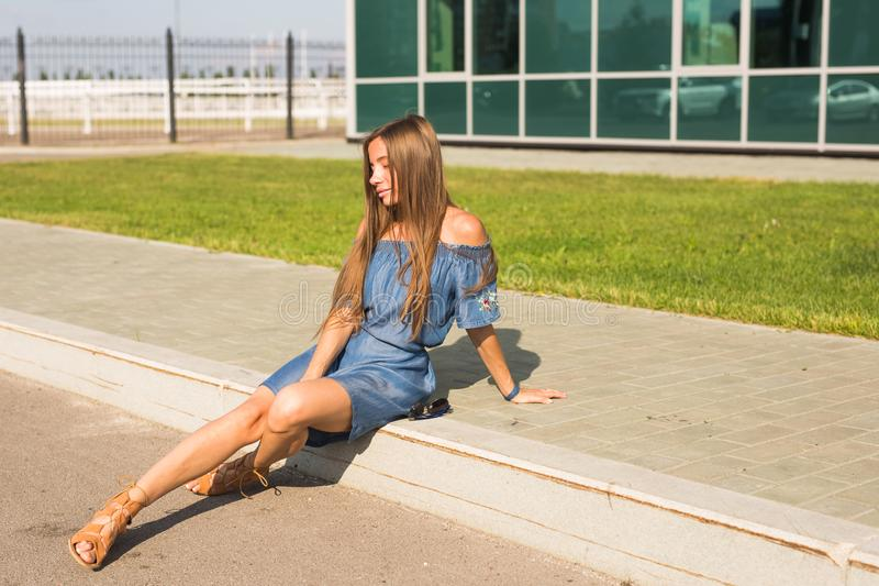 Girl sitting on street in summer day.  stock image