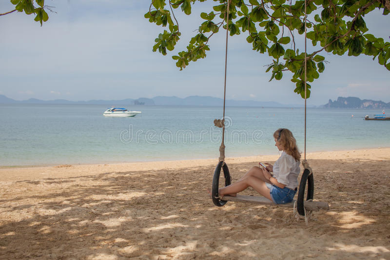 Girl sitting on the swing on the tropical beach stock photography