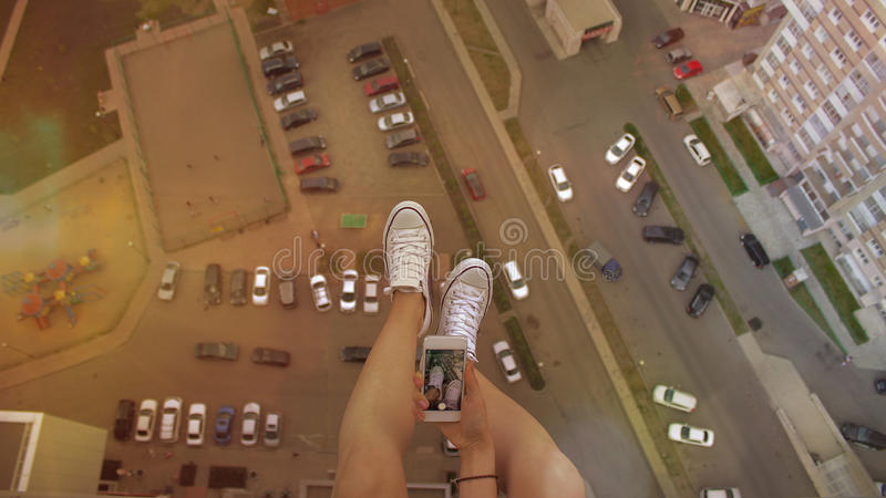 Girl sitting swinging her legs on a tall building with a telephone. Pictures of your feet. royalty free stock photography