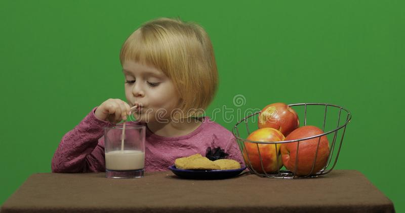 Girl sitting at the table with apples, cookies and drinks cacao. Chroma Key stock photos