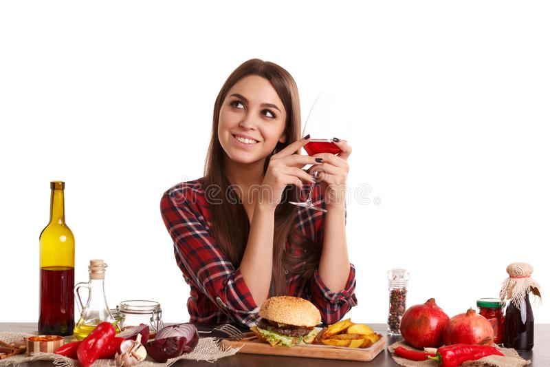 A girl sitting at table with food and holding a glass with wine, smiling and looking up. Isolated on white. royalty free stock photo