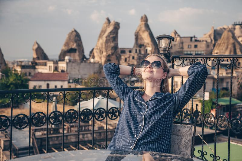 Girl sitting at the table on the roof terrace of cave hotel in Cappadocia, Turkey. Famous mountains and cave buildings stock image