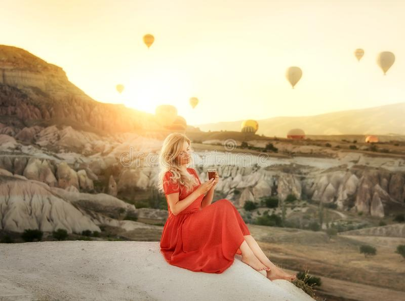 A girl sitting on the top of a cliff with a glass of Turkish tea at dawn with a view of the mountains of Cappadocia and balloons i stock photos