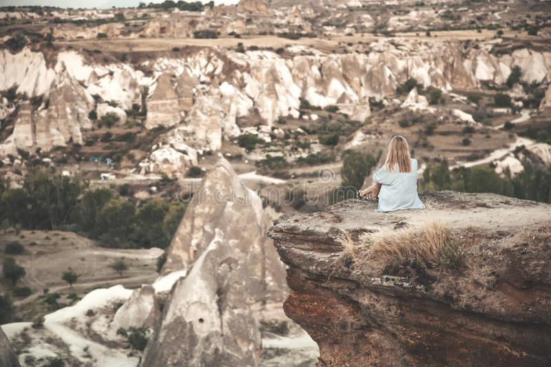 Girl sitting on the top of mountain in Cappadocia, Turkey. Aerial view on the famous stone peaks. Concept of travel and royalty free stock photography