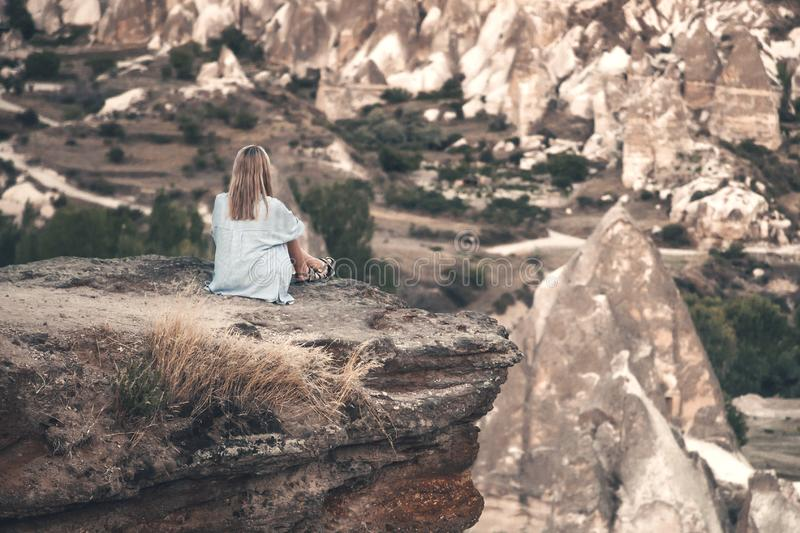 Girl sitting on the top of mountain in Cappadocia, Turkey. Aerial view on the famous stone peaks. Concept of travel and stock photography