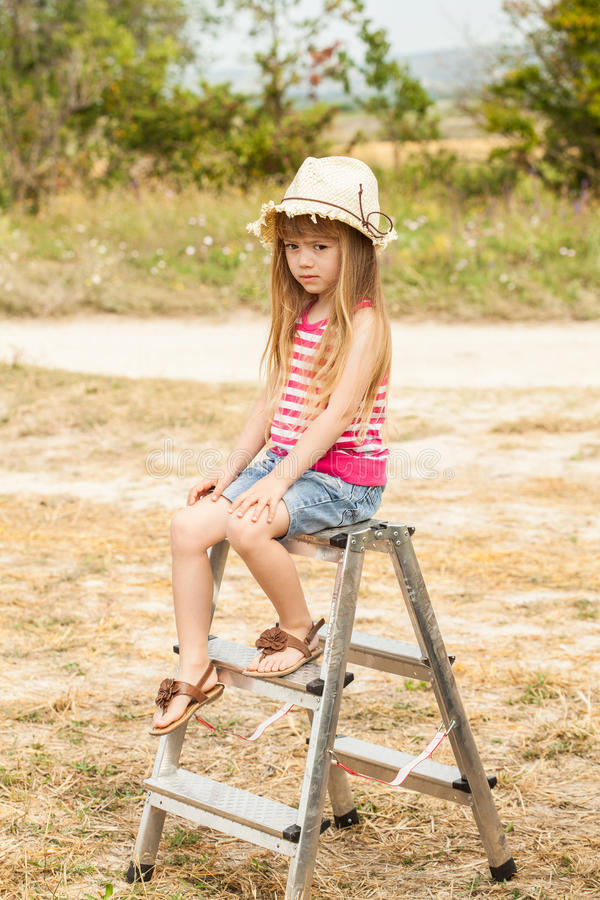 Girl sitting on top stepladder outdoors stock images