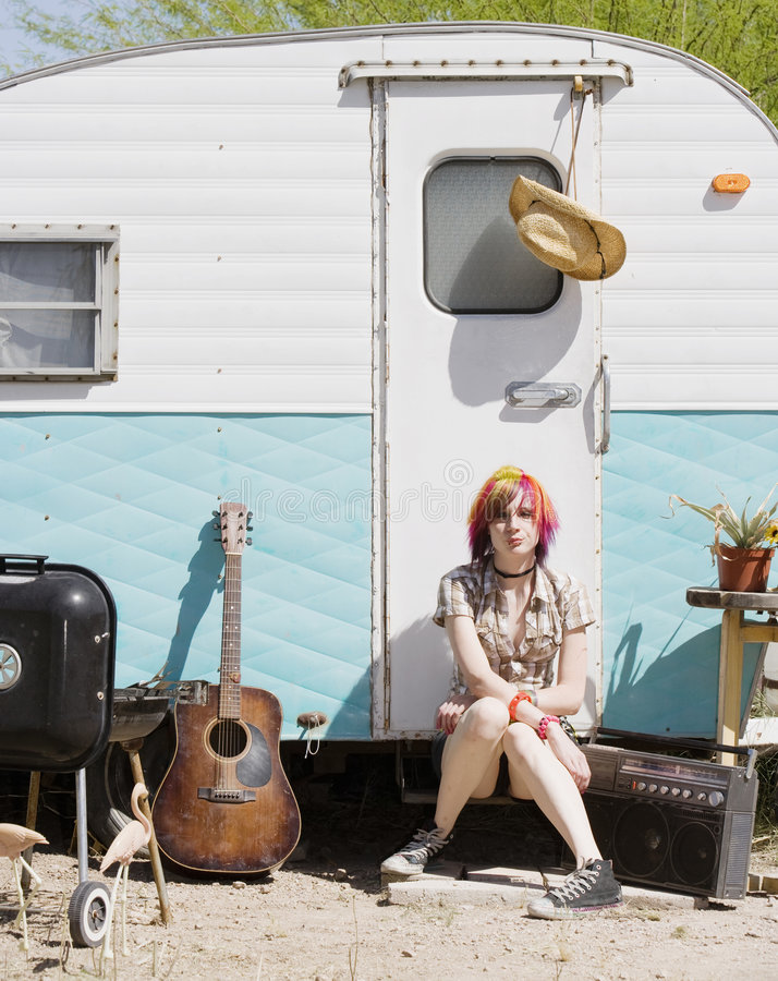 Girl Sitting on a Trailer Step. Punk girl with brightly colored hair sitting on a trailer step stock photography