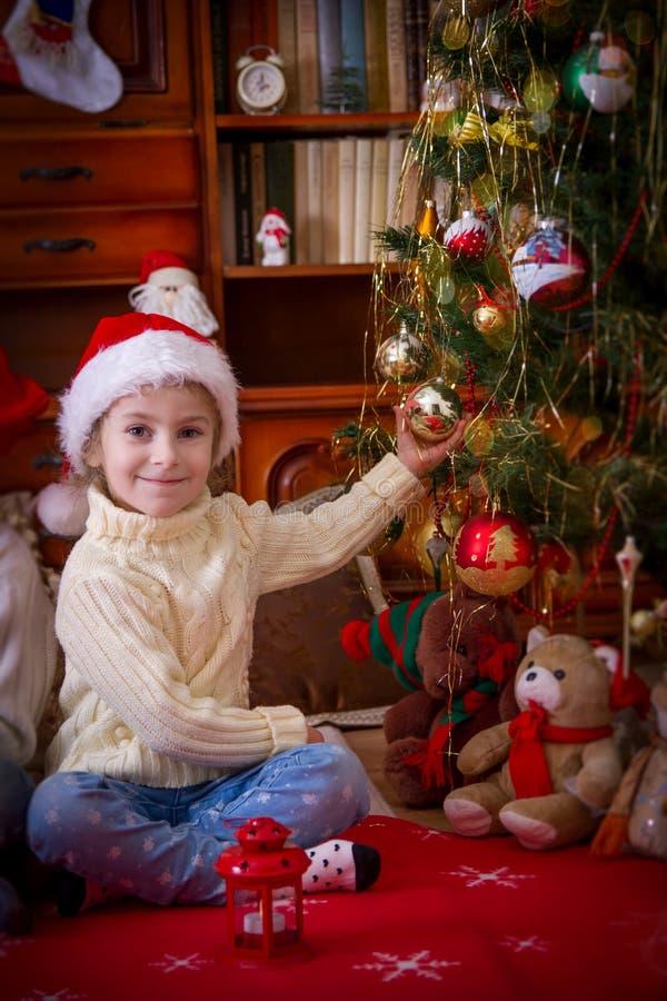 Girl sitting under Christmas tree holding ball royalty free stock photo