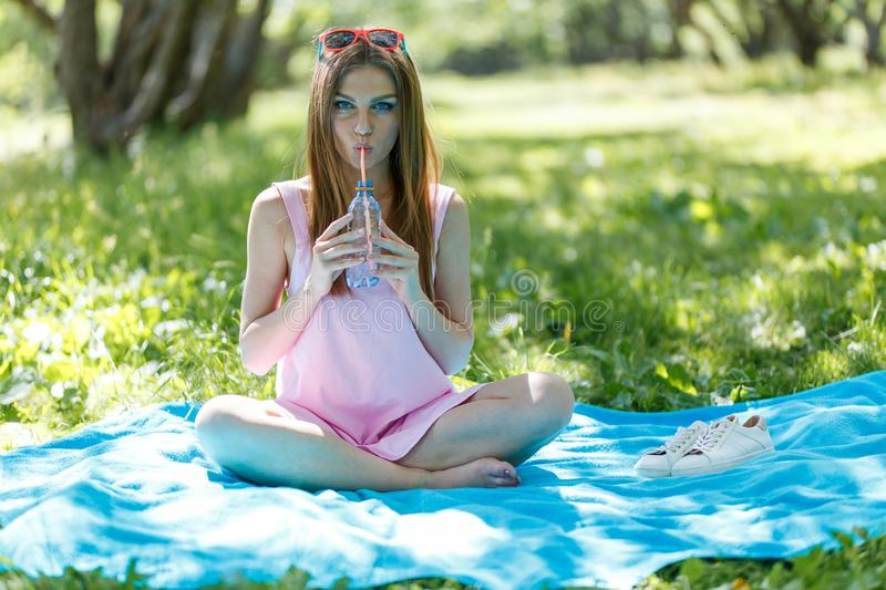 Beautiful girl sitting under the tree in nature and drinking fresh bottled water on sunny summer day. Girl sitting under the tree in nature and drinking fresh royalty free stock photos