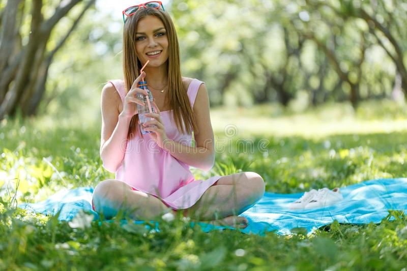 Beautiful girl sitting under the tree in nature and drinking fresh bottled water on sunny summer day. Girl sitting under the tree in nature and drinking fresh stock images