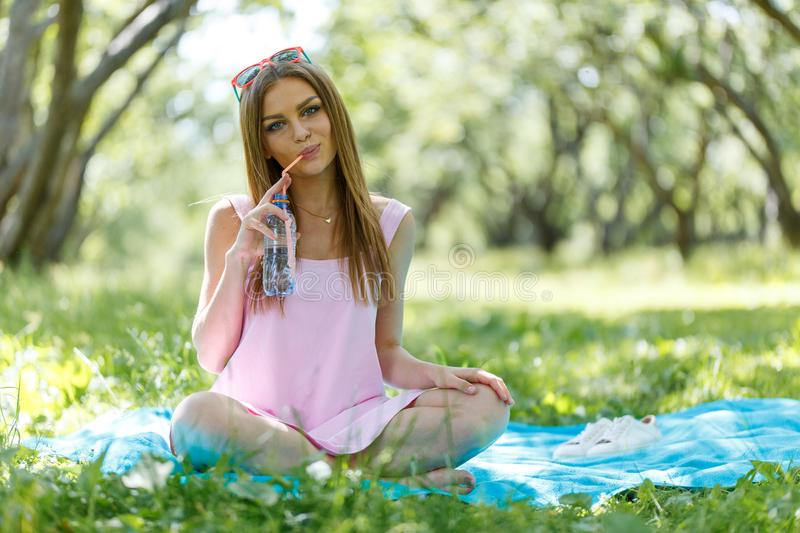 Beautiful girl sitting under the tree in nature and drinking fresh bottled water on sunny summer day. Girl sitting under the tree in nature and drinking fresh stock image