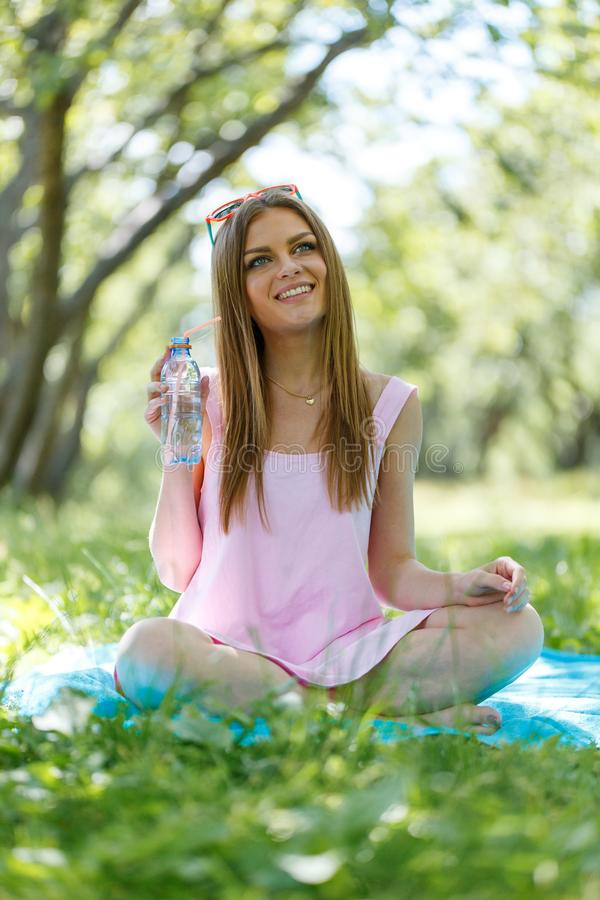 Beautiful girl sitting under the tree in nature and drinking fresh bottled water on sunny summer day. Girl sitting under the tree in nature and drinking fresh stock photography