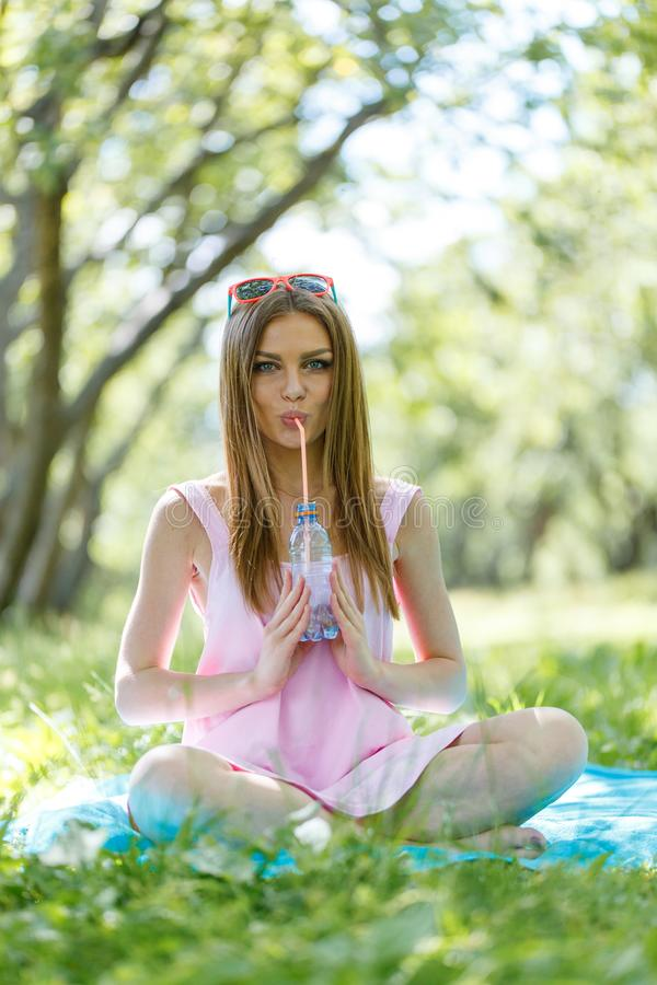 Beautiful girl sitting under the tree in nature and drinking fresh bottled water on sunny summer day. Girl sitting under the tree in nature and drinking fresh stock photo