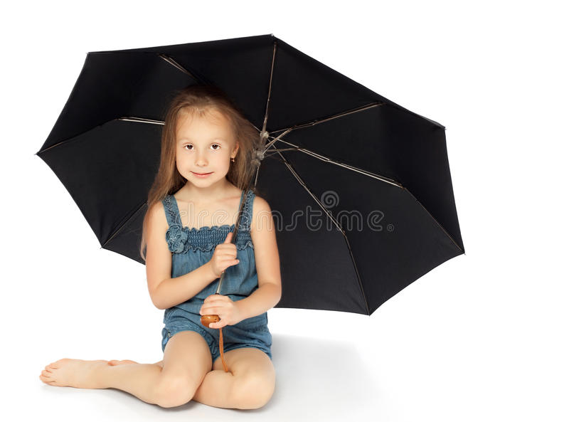 Girl sitting under an umbrella royalty free stock images