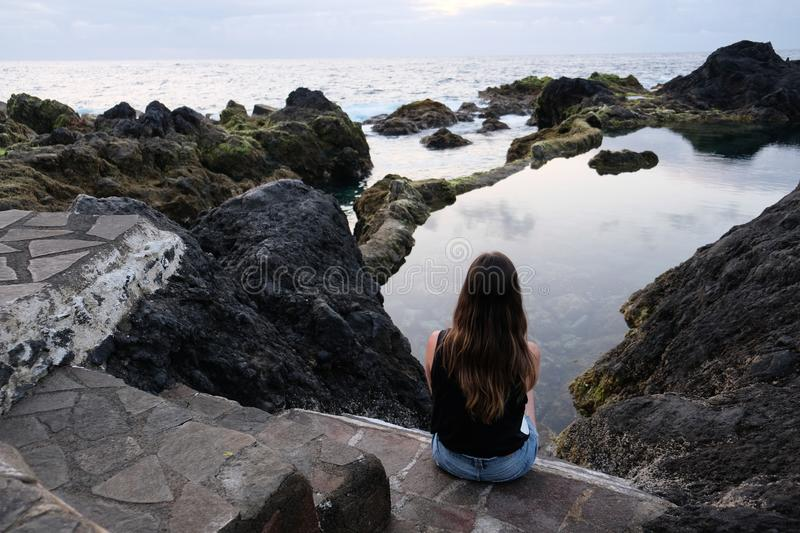 Girl sitting on volcanic rocks looking at natural pool and sea stock photography