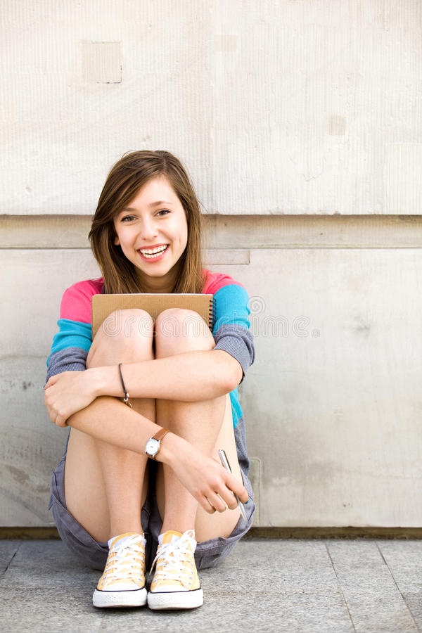 Girl Sitting By The Wall Royalty Free Stock Image