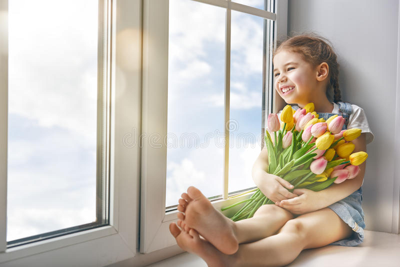 Girl sitting on the window stock photo