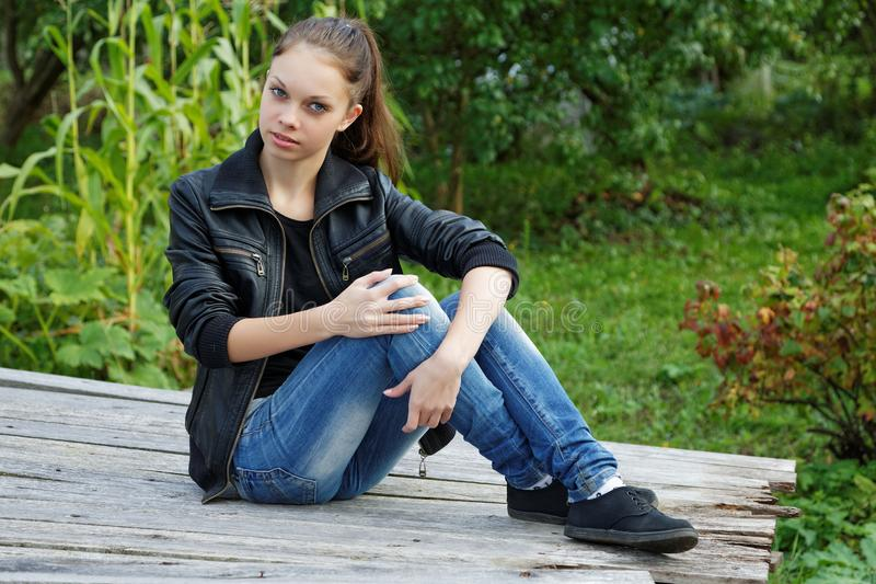The girl sitting on wooden boards royalty free stock images