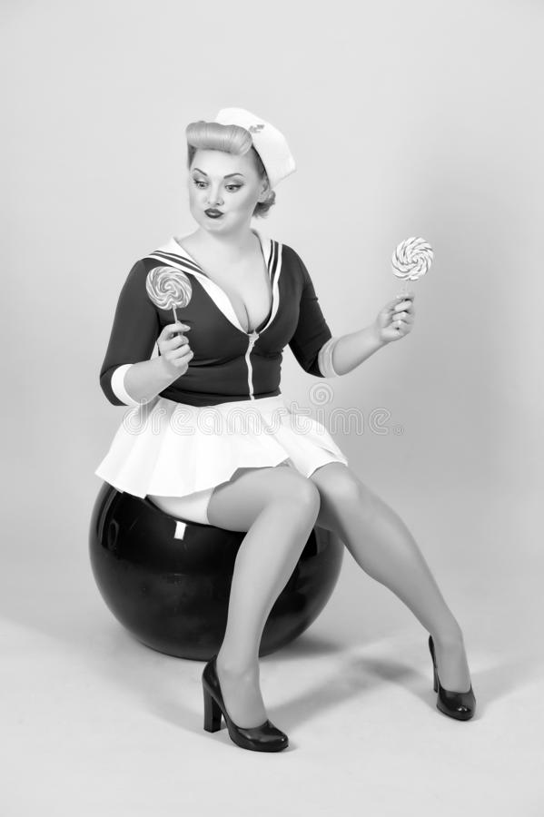 Girl size plus choosing between two lollipops. woman of pin-up royalty free stock image