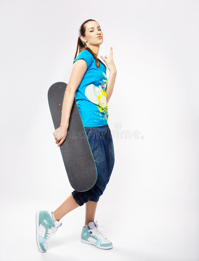 Girl with skateboard. Portrait of beautiful extreme girl with skateboard on gray royalty free stock photos