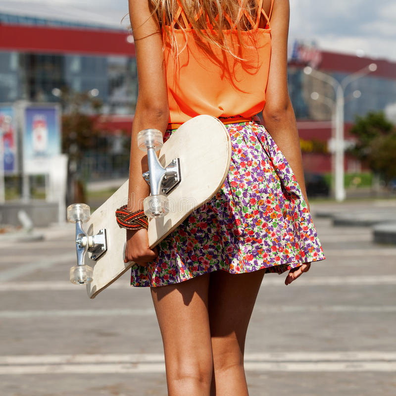 Girl with skateboard. Funky Girl with skateboard walking on street. Urban style. View from the back. Outdoors, lifestyle royalty free stock images