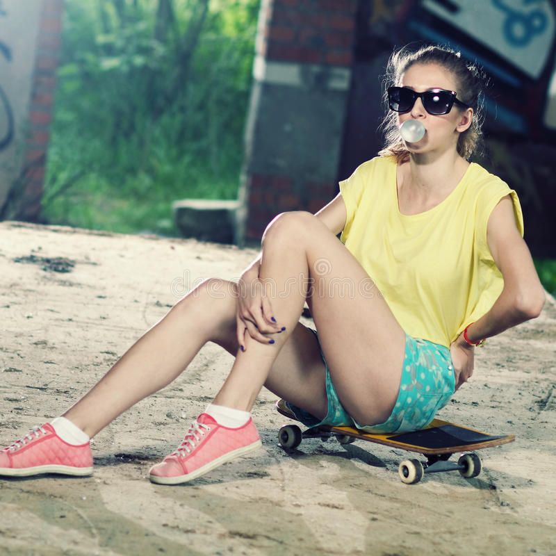 The girl on a skateboard. Modern hipster girl sitting on a skateboard and inflates gum royalty free stock photos
