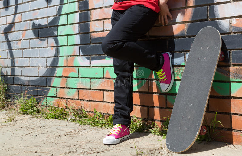 Girl with a skateboard. Next to a graffiti wall stock photo