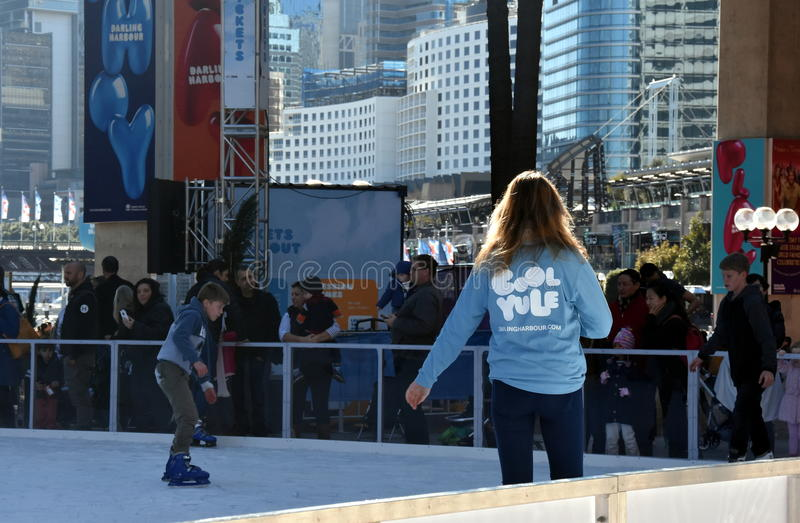 Girl skating on the ice rink in Darling Harbour stock photo