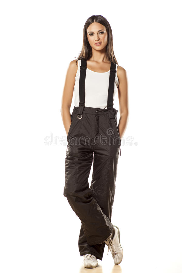 Girl in ski pants. Attractive girl posing in ski pants and sleeveless shirt on white background stock images