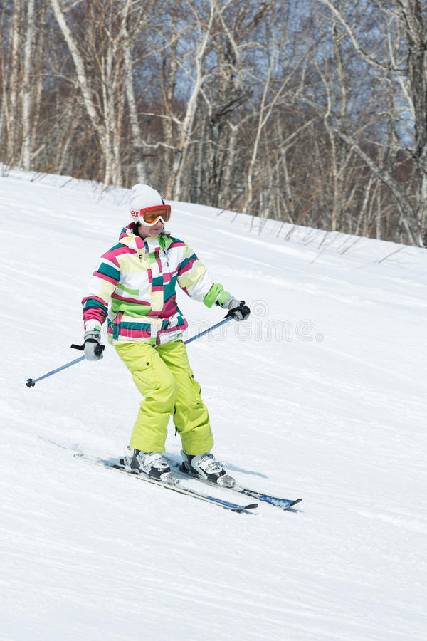 Girl skier coming down the slope on sunny day. MOROZNAYA MOUNTAIN, YELIZOVO, KAMCHATKA, RUSSIA - APRIL 17, 2015: Young woman skier in colorful outfit coming down stock photography