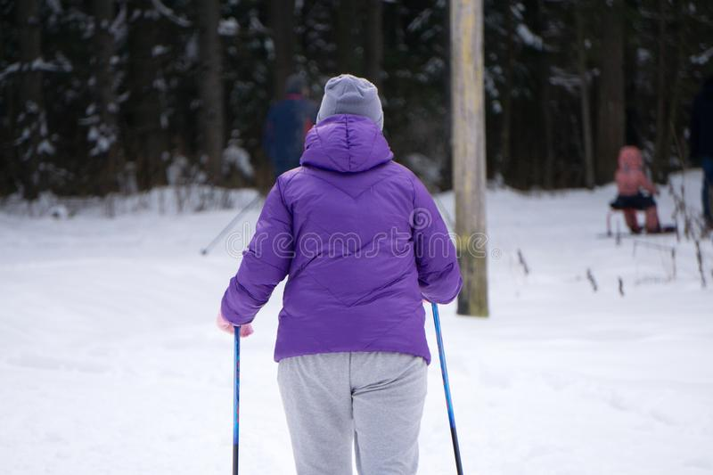 Girl skiing during snowfall weather ski resort Skier wears a blue winter coat, purple hot pants, blue shorts and white gloves. The. Tree covers the snow stock photography