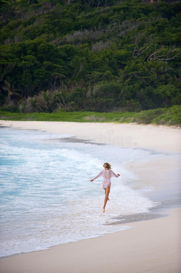 Girl skipping along the shore,seychelles.