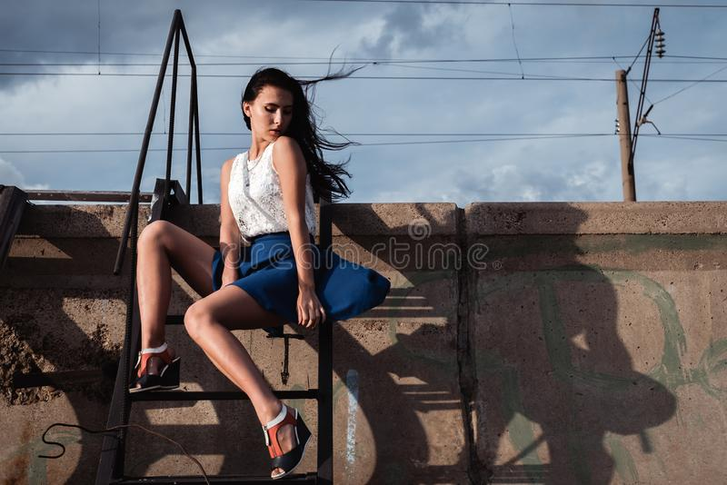 Girl in skirt sitting on the iron stairs bent legs. The wind is blowing through her hair. Behind concrete and clouds royalty free stock photo