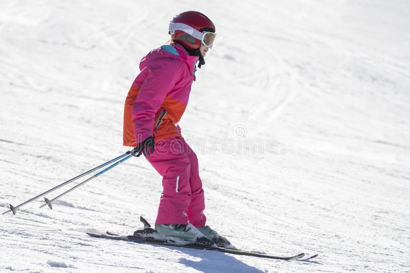 Girl on skis in soft snow on a sunny day royalty free stock image