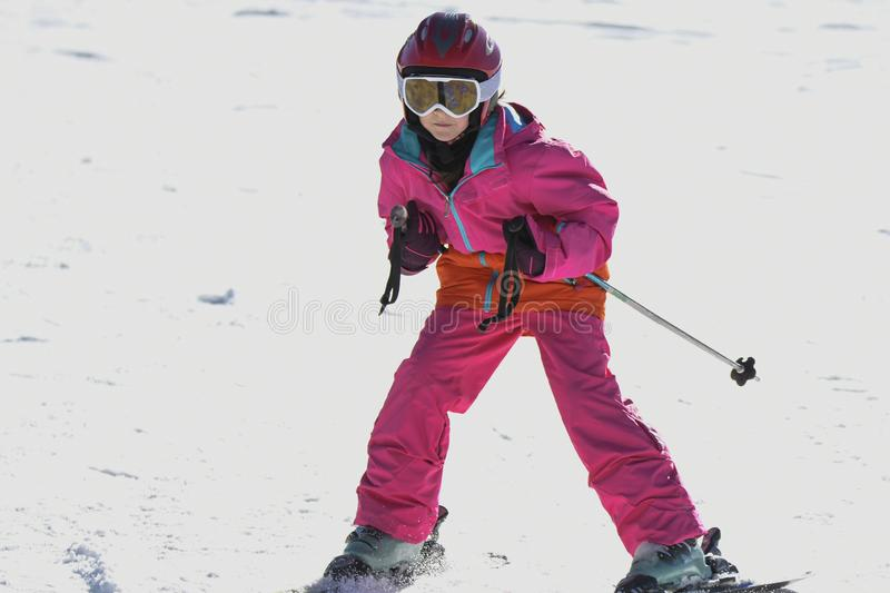 Girl on skis in soft snow on a sunny day stock images